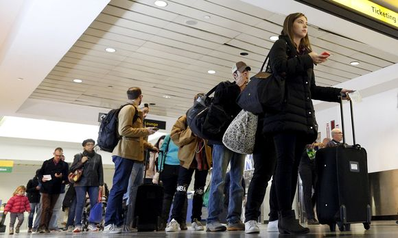 Travelers wait in line at a security checkpoint at La Guardia Airport in New York