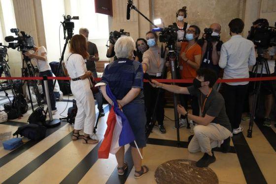 Нападател с френско знаме отговаря пред репортери, когато пристига в специална съдебна зала в сряда.