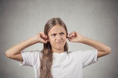 Annoyed girl covering her ears loud noise upstairs Royalty Free Stock Photos