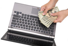 Person counting money over his computer.