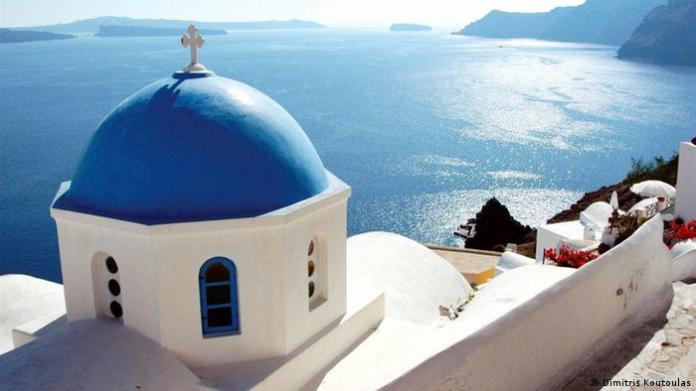 a white church with a blue dome on the island Santorini, Greece (Dimitris Koutoulas)