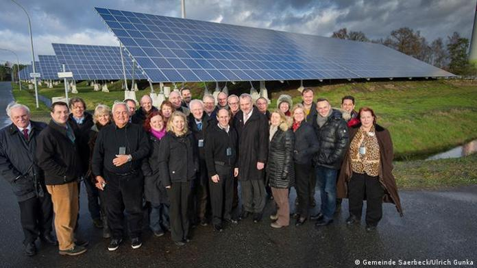 Group photo in the city of Saerbeck with visitors from the US in front of a solar panel park