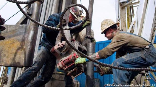 Two men working on heavy equipment at a drilling station