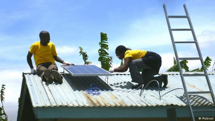 A man and a woman install a solar panel atop a home in Tanzania