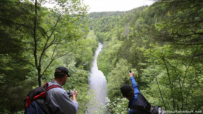 Two hikers taking pictures of the Wutach Gorge in the Black Forest, Germany