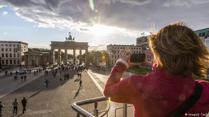 A woman taking a picture of the Brandenburg Gate in Berlin, Germany