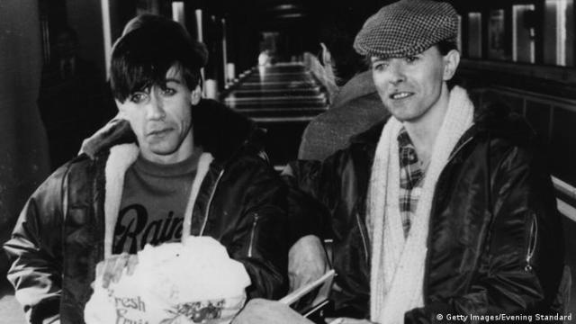 David Bowie (right) and Iggy Pop sit in leather jacks