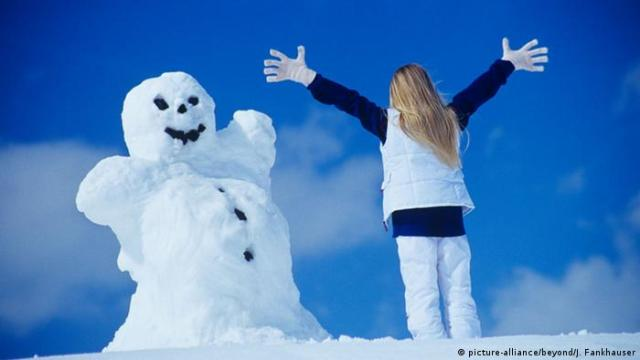 A woman facing a snowman (Photo: picture-alliance/beyond/J. Fankhauser)
