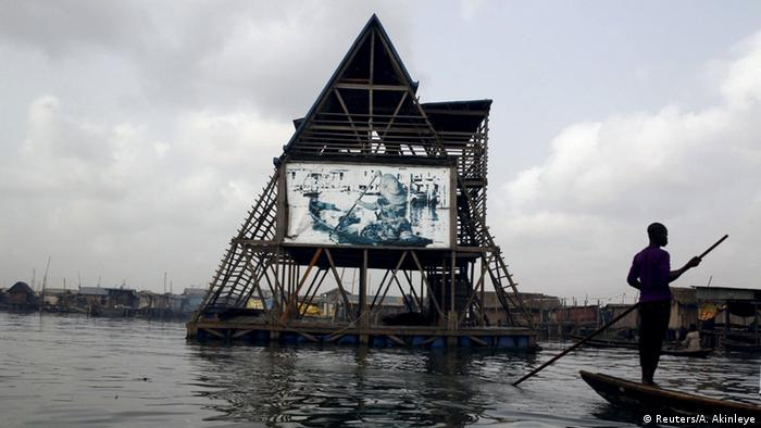 A-shaped Makoko Floating School building on water, with man on boat to the right