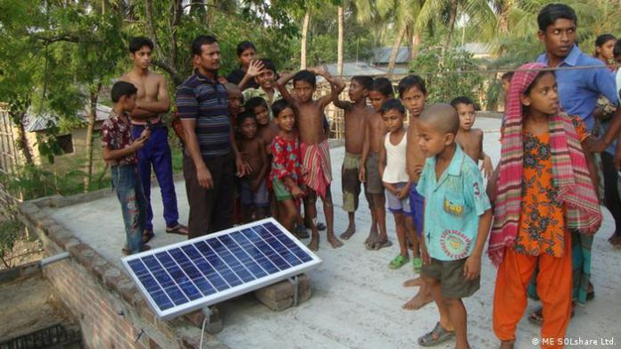 Adults and children with a microgrid solar panel on a flat roof in Bangladesh