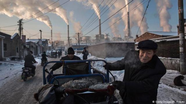 Smoke billows from stacks as Chinese men pull a tricycle in a neighborhood next to a coal fired power plant