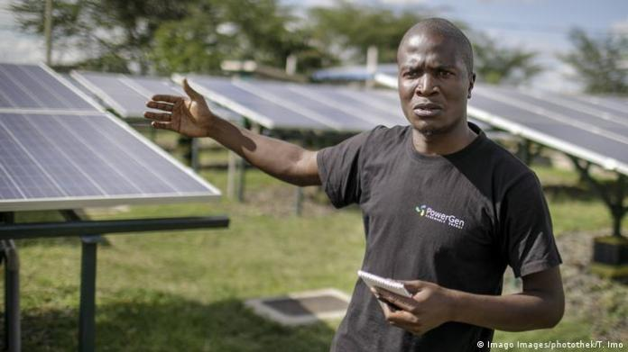 George Ndubi stands in front of the solar panels