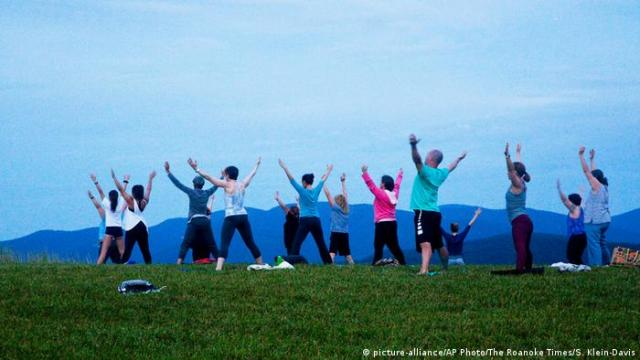 A group of people practicing yoga outdoors on a grassy hilltop