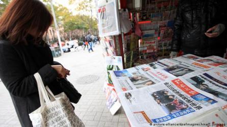 Residente de Xangai, na China, em frente a uma banca com jornais sobre a morte do líder norte-coreano Kim Jong Il, em 19 de dezembro de 2011.