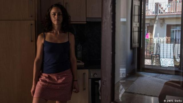 A woman standing in her apartment
