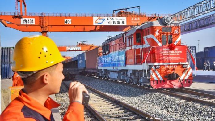 A freight train departs from a railway port in Latvia as a worker watches