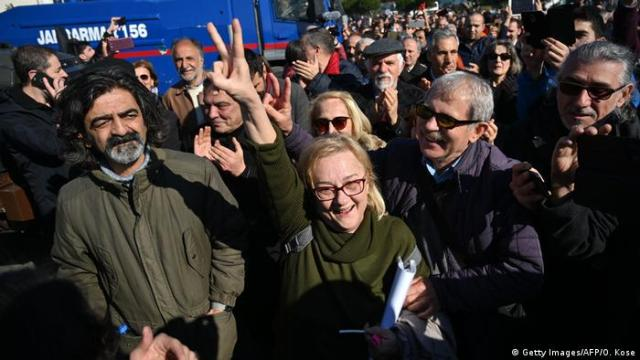 A mass of people smiling, clapping, and a woman showing a victory sign: Supporters celebrate in Istanbul after Osman Kavala's acquittal on February 18, 2020.