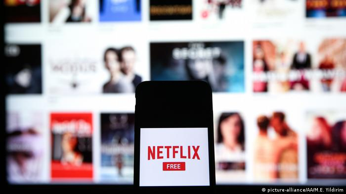 In this photo illustration a mobile phone screen displays the Netflix logo in front of a computer screen showing Netflix series and movies screen in Istanbul