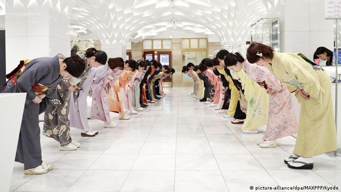 Employees dressed in kimonos practice a greeting bow ahead of the opening of a New Year sale at a Mitsukoshi department store in Tokyo (picture-alliance/dpa/MAXPPP/Kyodo)