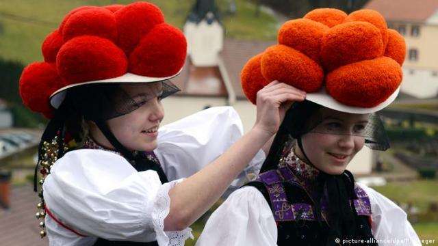 Two girls wearing traditional Black forest Bollenhut pompom hats