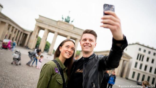 A couple poses for a photo in front of the Brandenburg Gate in Berlin, Germany (picture-alliance/dpa/K. Nietfeld)