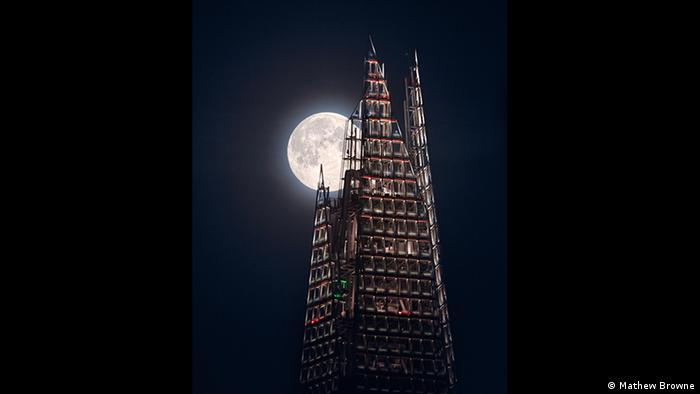 A full moon appears behind the slightly illuminated facade of a high-rise building (Photo: Mathew Browne).