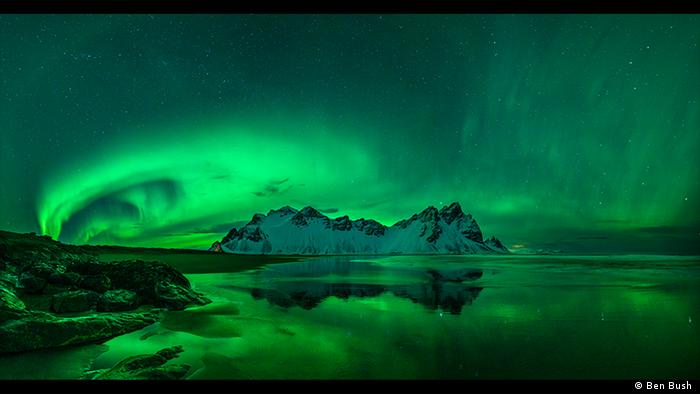 Night sky with water in the foreground, snow-capped mountains in the background, honeycomb neon-green northern lights in the sky (Photo: Ben Bush).