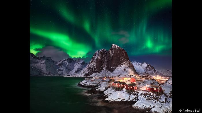 Night shot of a small coastal settlement with red houses and snow-capped mountains.  Shimmering green lights can be seen in the sky (Photo: Andreas Ettl).