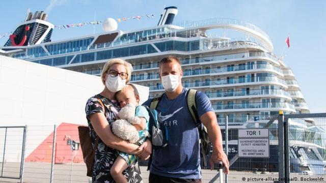 Passengers with masks on the dock next to the Mein Schiff 2 in August 2020