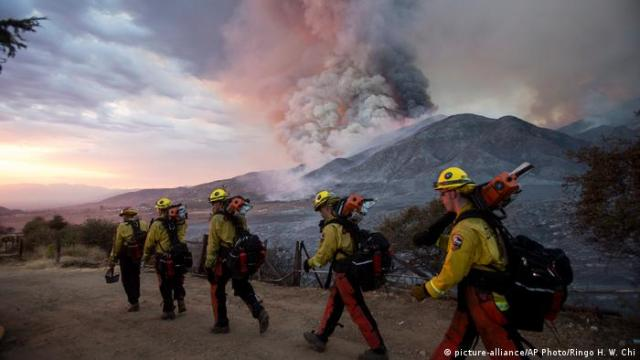 Firefighters walk towards clouds of smoke in the mountains