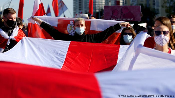 People hold large red and white flags of the Belarus opposition.
