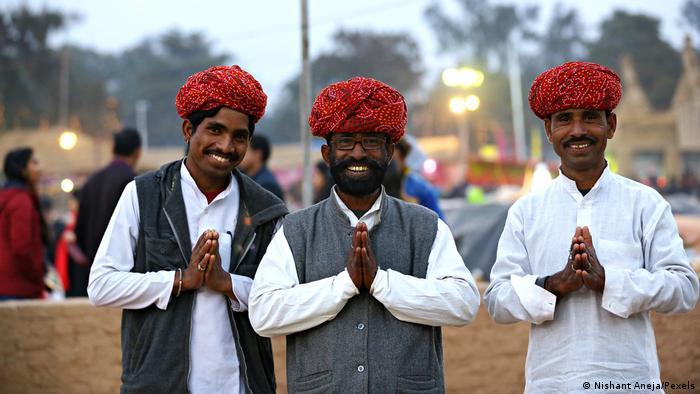 Tres hombres indios sonríen a la cámara y saludan