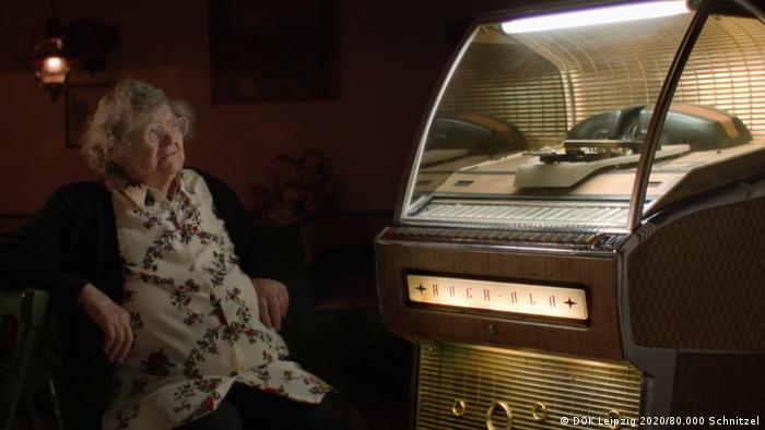 A senior woman sitting next to a jukebox (photo: DOK Leipzig 2020/80.000 Schnitzel).