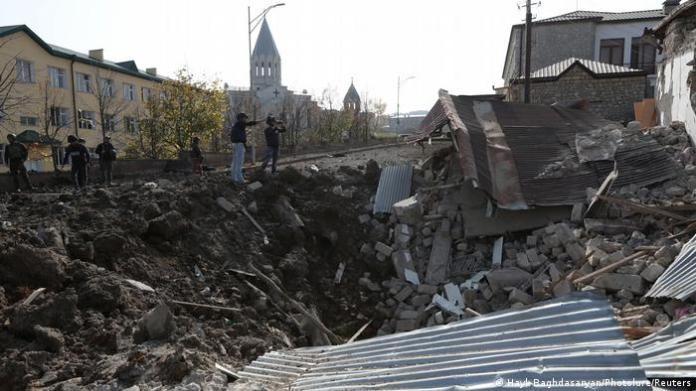 Ruins of destroyed buildings, several people and a church spire in the background in the city of Shusha in Nagorno-Karabakh
