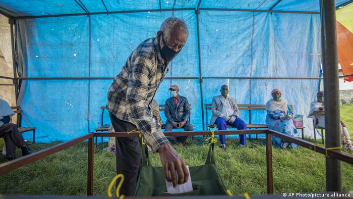 A man puts a ballot paper in a ballot box during the TPLF election