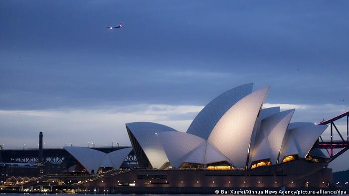 Airplane flies over Sydney Opera House, Australia