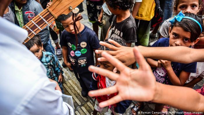 En Caracas, los niños extienden desesperadamente los brazos cuando Caritas u otras organizaciones distribuyen alimentos. Muchos no han comido en días. El 96% de los hogares en Venezuela viven en la pobreza, 64% en pobreza extrema, según un estudio de la Universidad Católica Andrés Bello. La carne, el pescado, los huevos, las frutas y las vegetales solo se sirven en muy pocas familias.