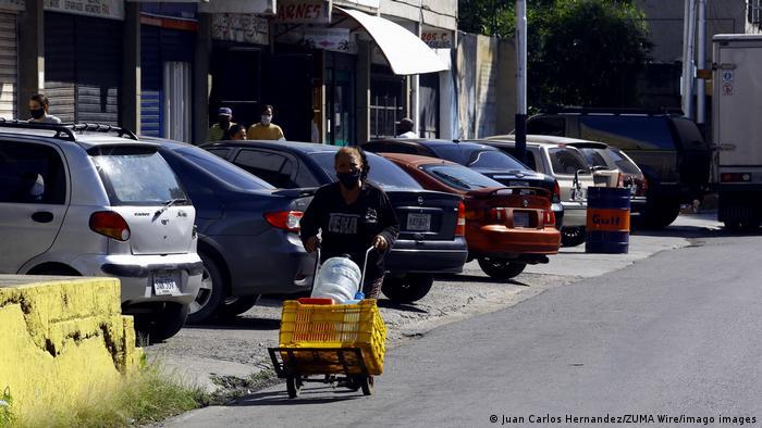 En Guacara, en el estado Carabobo, una residente camina por las calles con recipientes de plástico en busca de agua potable. En algunos lugares de Venezuela solo hay unas pocas horas de agua corriente tres días a la semana. Por esta razón, muchas familias llenan rápidamente todas las botellas y frascos que encuentren para tener un poco de agua cuando la sequía vuelva.