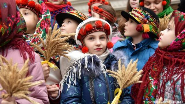 A girl in traditional Ukrainian dress holds a bunch of wheat