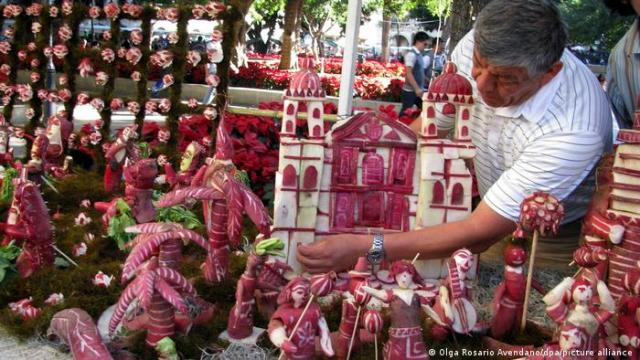 A man tending to his display of a church and figures made of carved radishes