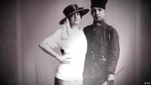 a women in a hat and a man dressed as a soldier pose together for a photo