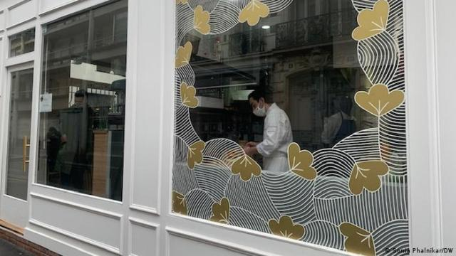 Chef Mory Sacko's restaurant in southern Paris, photographed from outside. A cook in a face mask is seen through the front window.