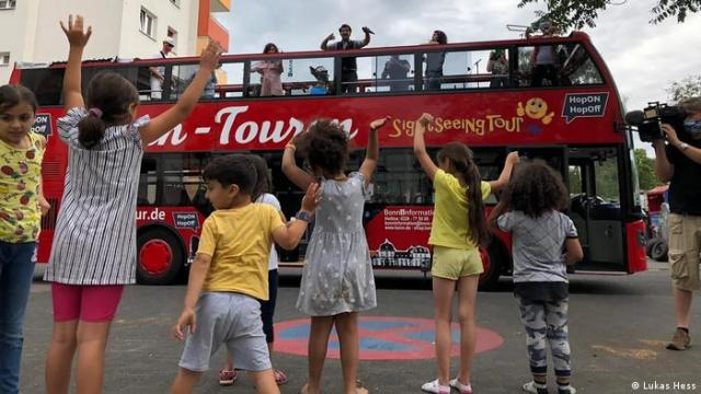 Saman Haddad and the musicians of the Kültürklüngel Orkestar on a red tourist bus, surrounded by dancing kids