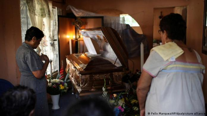Relatives and friends in mourning by open casket of journalist Candido Rios Vazquez