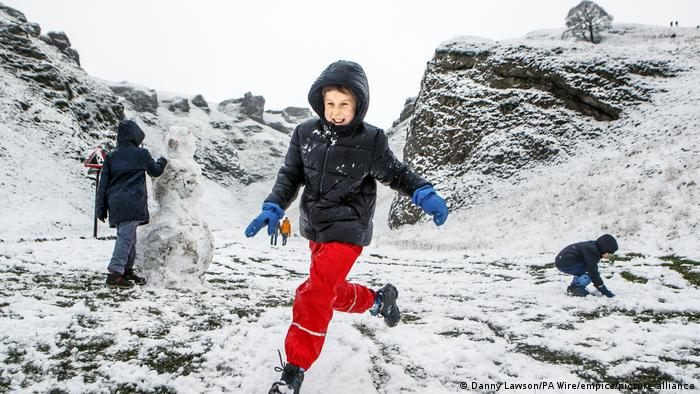 Young children play in the snow in England