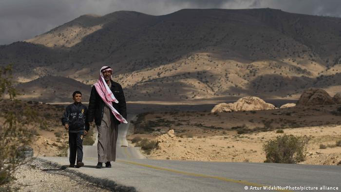A man with young boy walk on the road between Uum Sayhoun Bedouin village and Al-Baydha, located near the ancient city of Petra