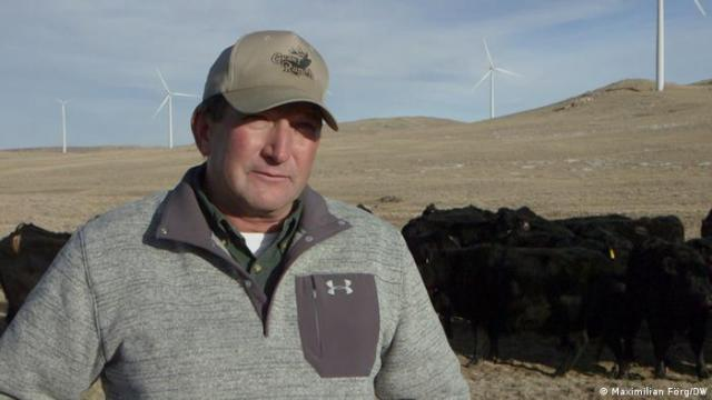 Rick Grant stands in front of wind turbines on his property