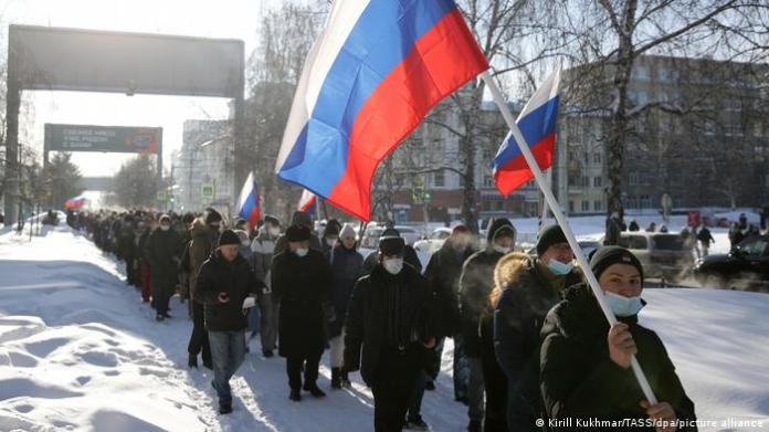 Protesters holding the Russian flag march down a snow-covered street in Novosibirsk