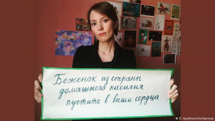 Apakhonchich holding a banner in Russian that translates as: 'Refugees from the lands of domestic violence — let them into your heart'