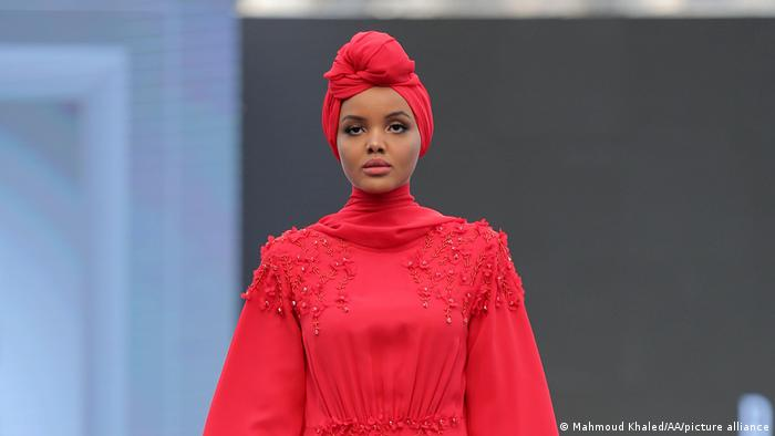 The American model Halime Aden in red robe and turban-like head-covering at Dubai's Modest Fashion Week 2017.